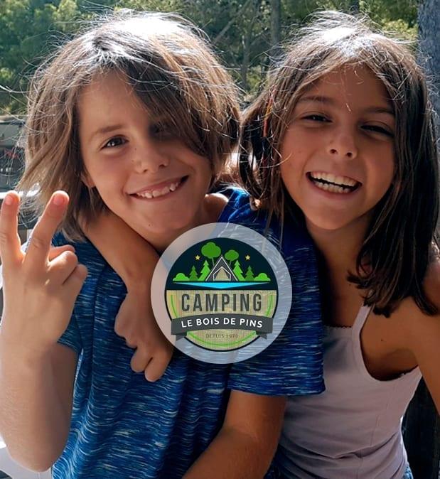 Logo du camping le bois de pins avec deux enfants sur la terrasse d'un Mobil-Home - Camping Le bois de pins - Perpignan 66